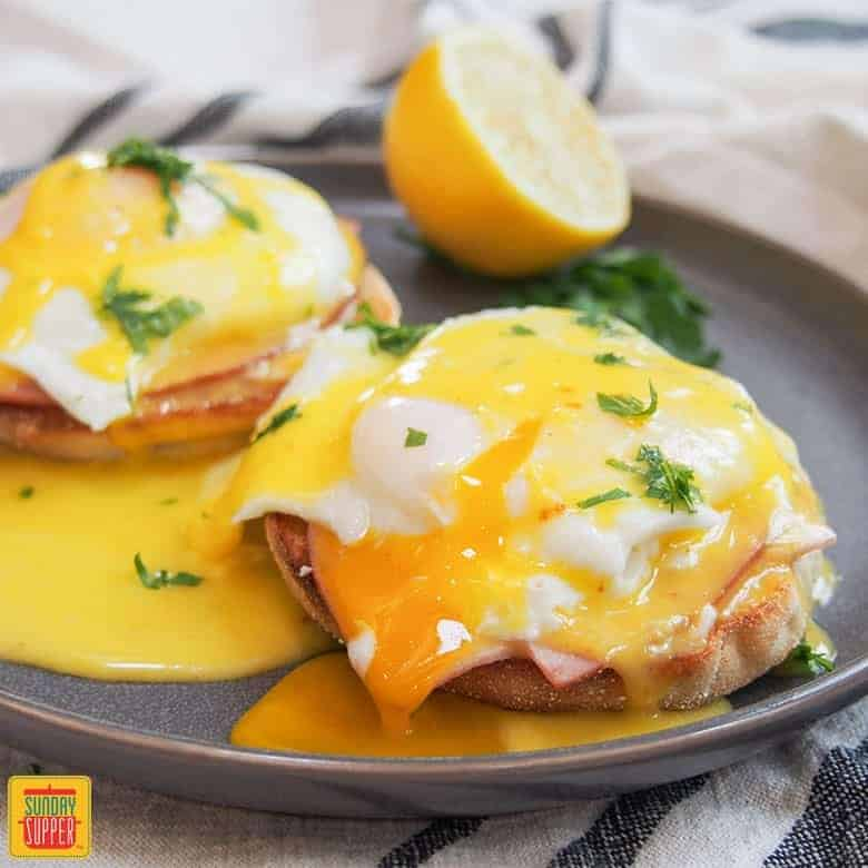 How to Make Eggs Benedict: completed eggs benedict on silver plate with hollandaise sauce and lemon