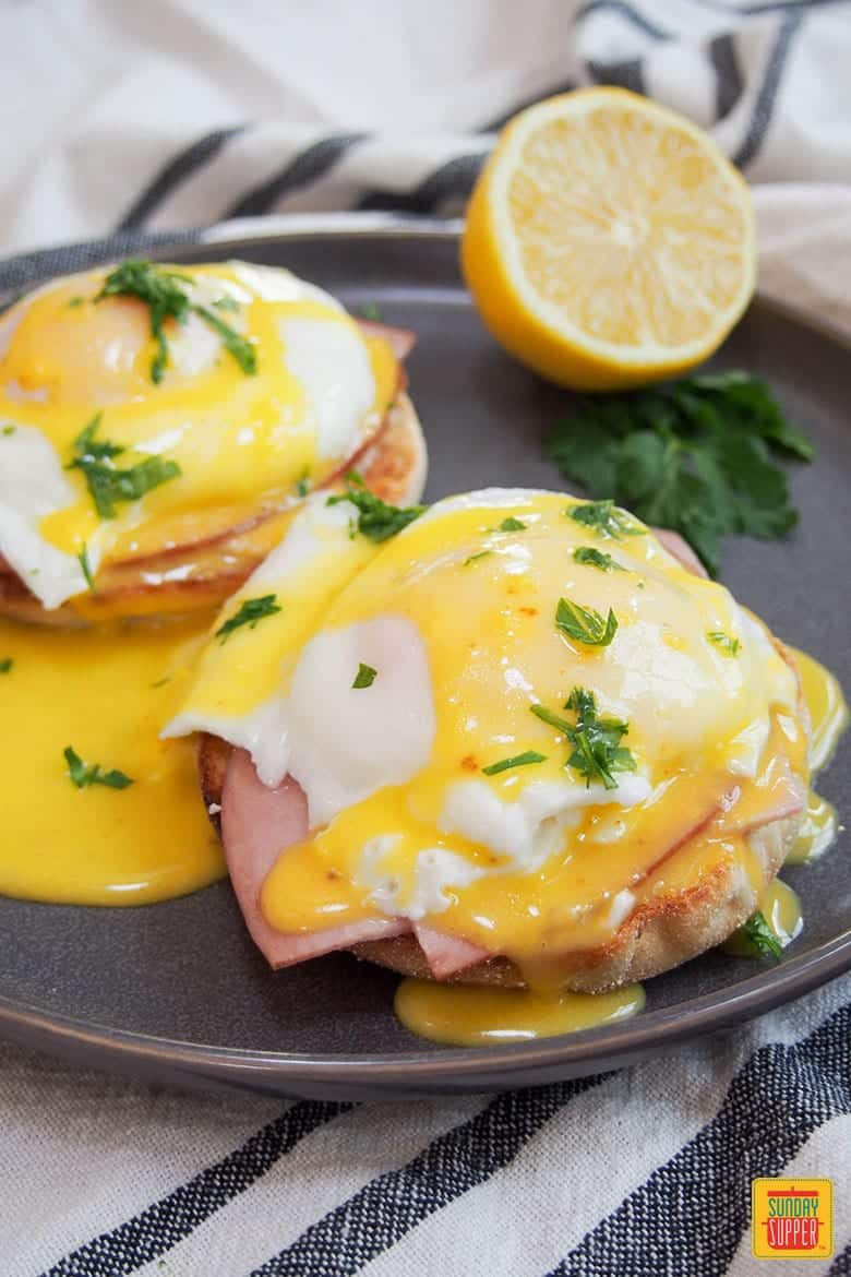 How to Make Eggs Benedict: eggs benedict on silver plate with lemon, topped with hollandaise sauce and ready to eat