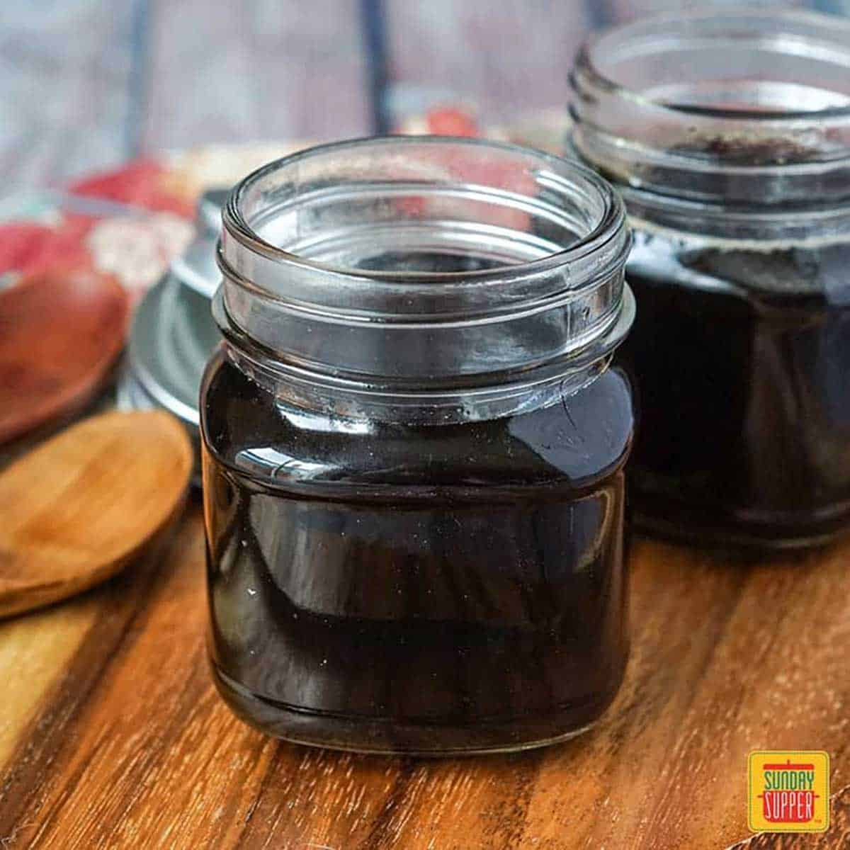 Homemade teriyaki sauce in two glass jars on a wooden surface
