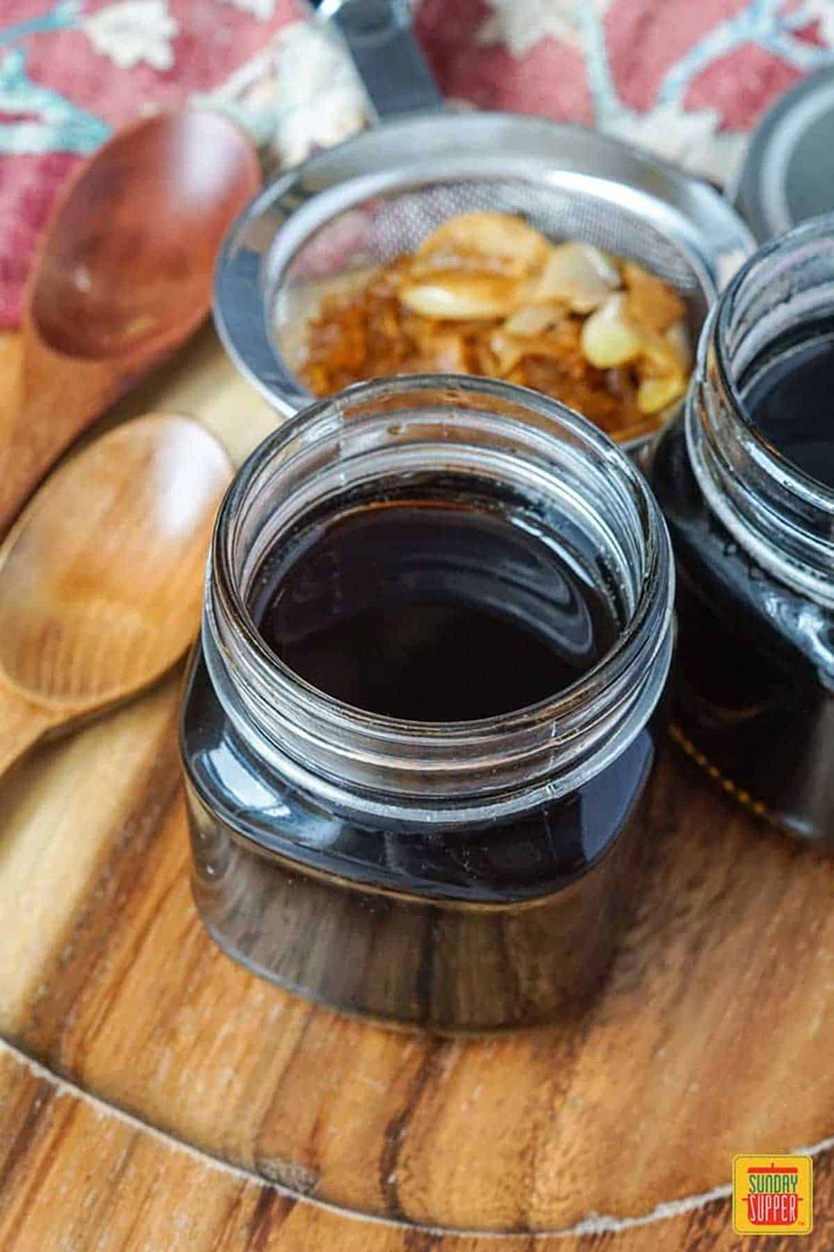 Homemade teriyaki sauce with strained onion, ginger, and garlic in two glass jars