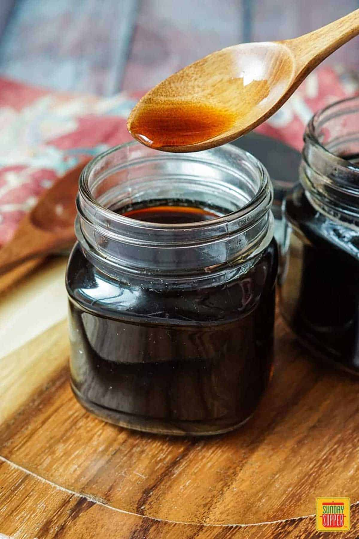 Pouring homemade teriyaki sauce into a glass jar using a wooden serving spoon