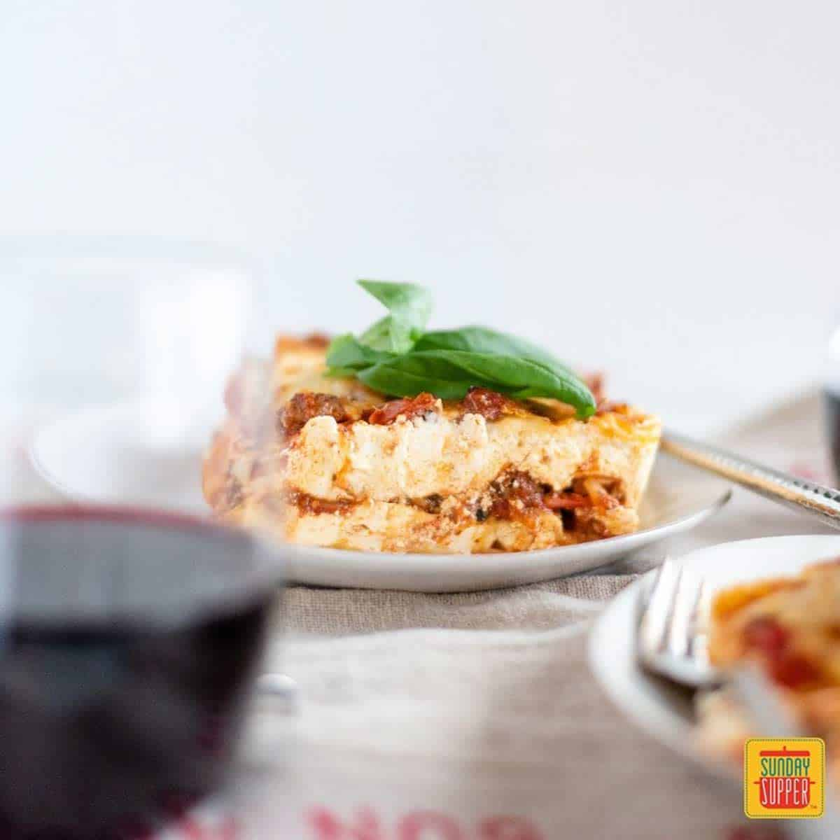 Lasagna for two on a plate with a glass of red wine