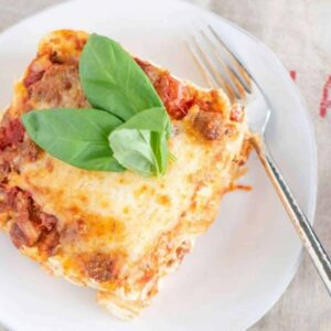 Lasagna for two on a plate with fresh basil