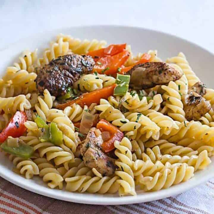 Rasta pasta recipe with jerk chicken, bell peppers, and fusilli pasta served on a white plate, ready to eat