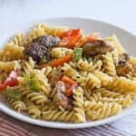 Rasta pasta recipe for two with jerk chicken, bell peppers, and fusilli pasta served on a white plate, ready to eat