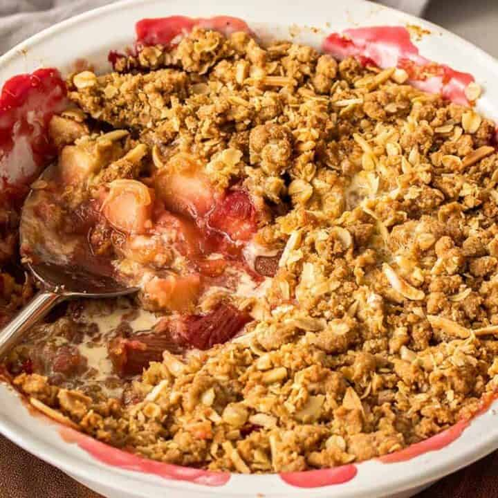 A white pie dish filled with a fruit crumble with a spoon in the side
