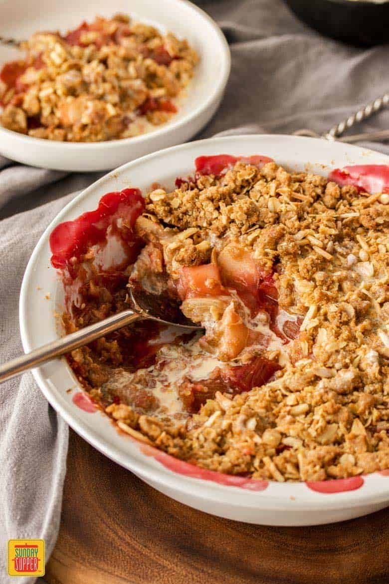 A rhubarb and apple crumble in a pie dish with a small serving in the background