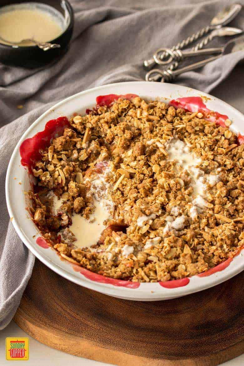 A close up of rhubarb and apple crumble drizzled with cream