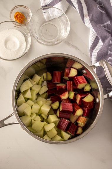 A saucepan filled half with chopped apple and half with chopped rhubarb