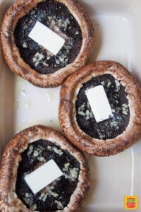 baked portobello mushrooms with slices of butter, ready to bake