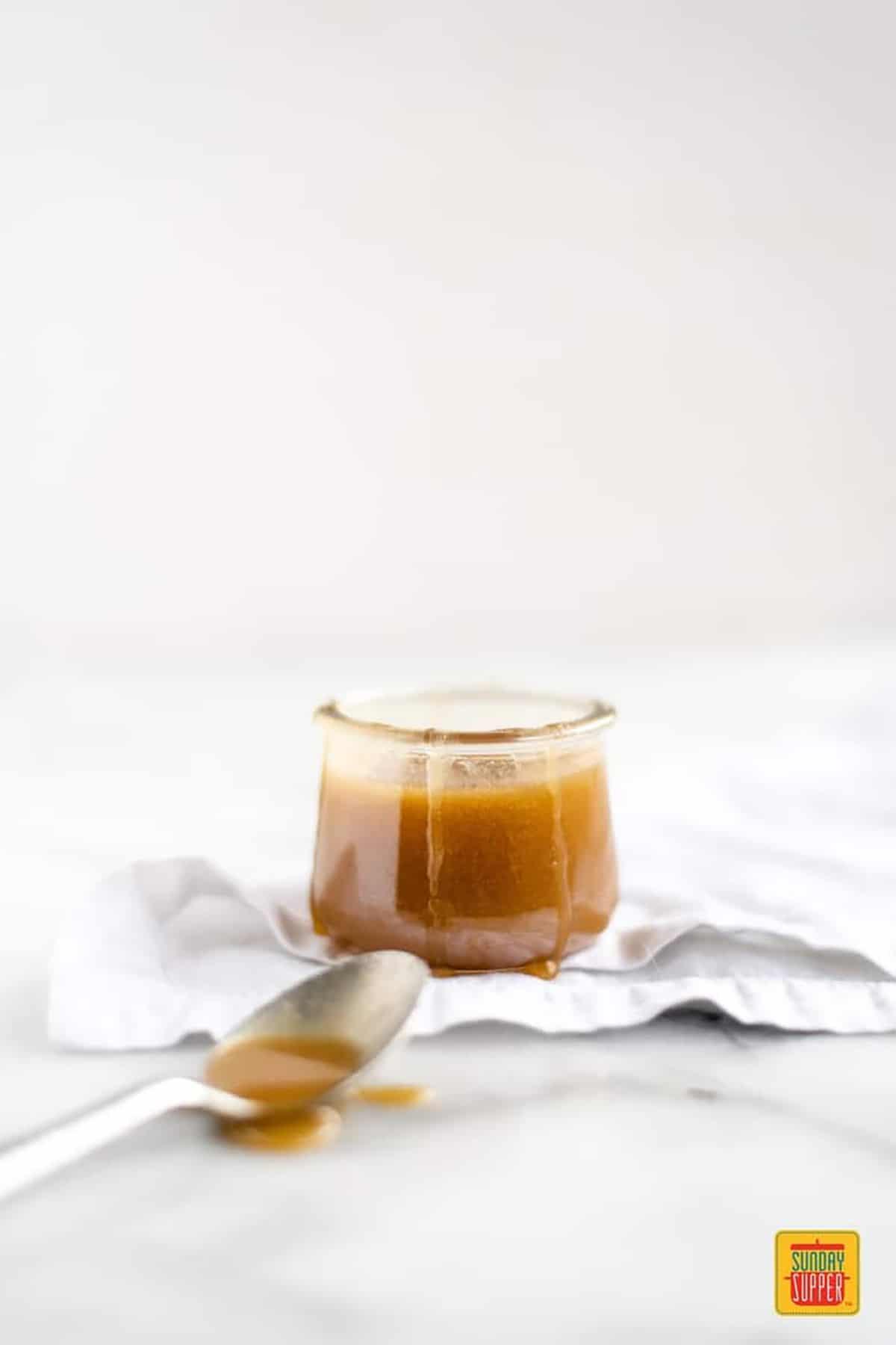 A spoon of butterscotch sauce near a jar of butterscotch
