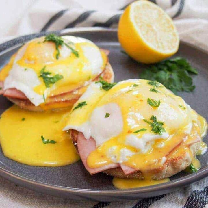 Eggs benedict on a black plate with fresh citrus