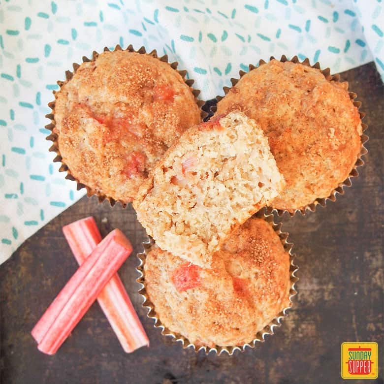 Three Rhubarb Muffins with a fourth muffin stacked on top, half eaten, next to fresh rhubarb