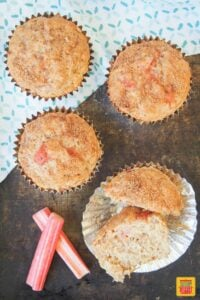 Four rhubarb muffins: one is split in half in a muffin mold to show how soft it is