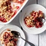 two servings of strawberry rhubarb crisp on small white plates. There is a 9x9 dish sitting beside the plates.