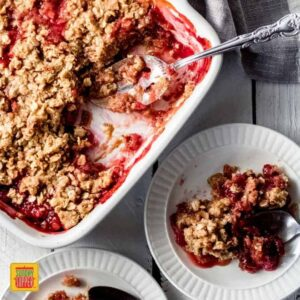 A 9x9 white dish with strawberry rhubarb crisp. There are two servings spooned out onto white plates.