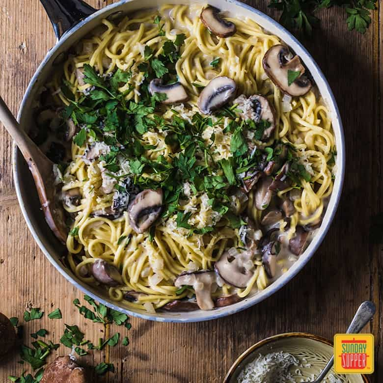 Creamy mushroom pasta in a skillet with a fork