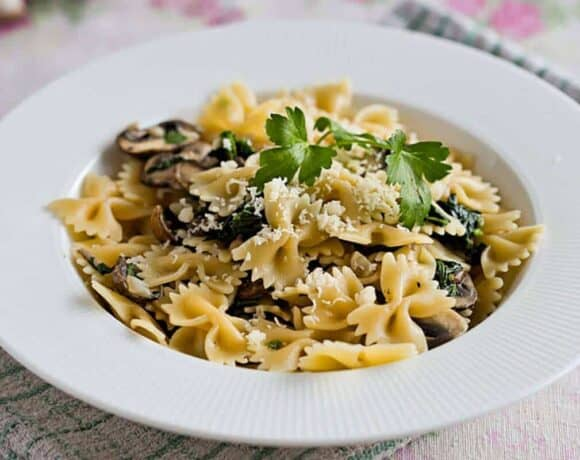 Mushroom spinach pasta on a white plate with parmesan on top