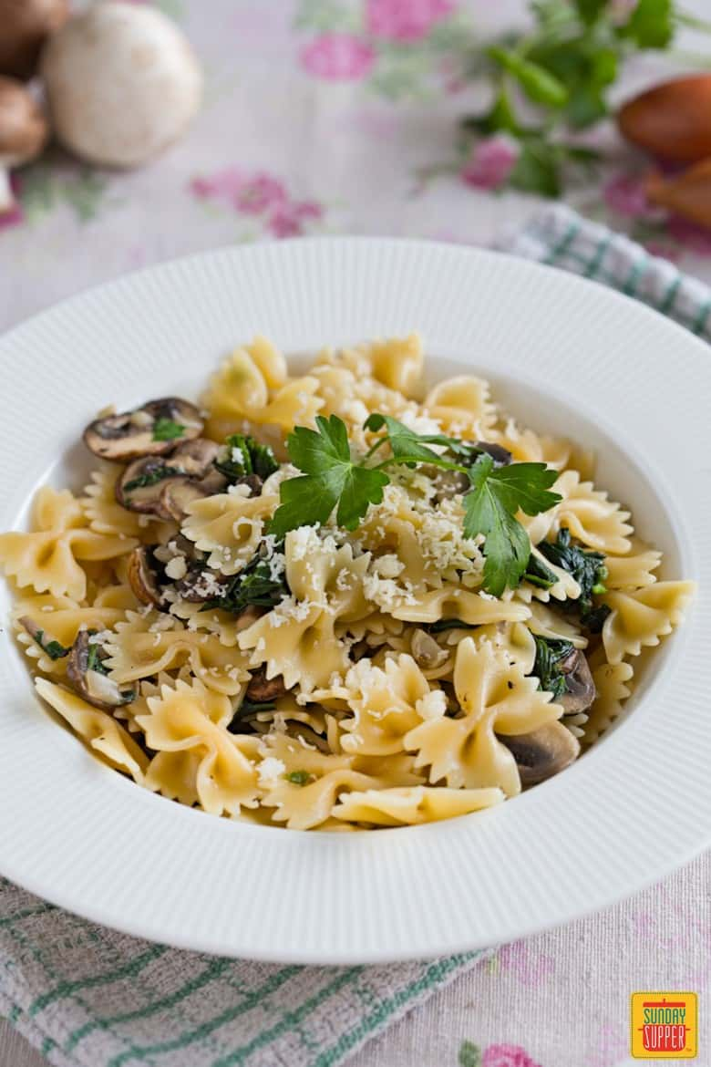 Mushroom Spinach Pasta on a white plate topped with parmesan