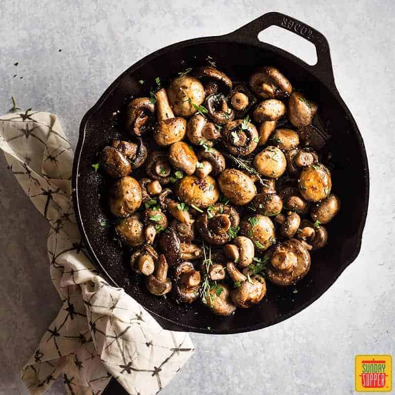 Button mushrooms in a cast iron skillet, cooked and ready to serve, the handle of the skillet is wrapped in a towel with a hexagon pattern