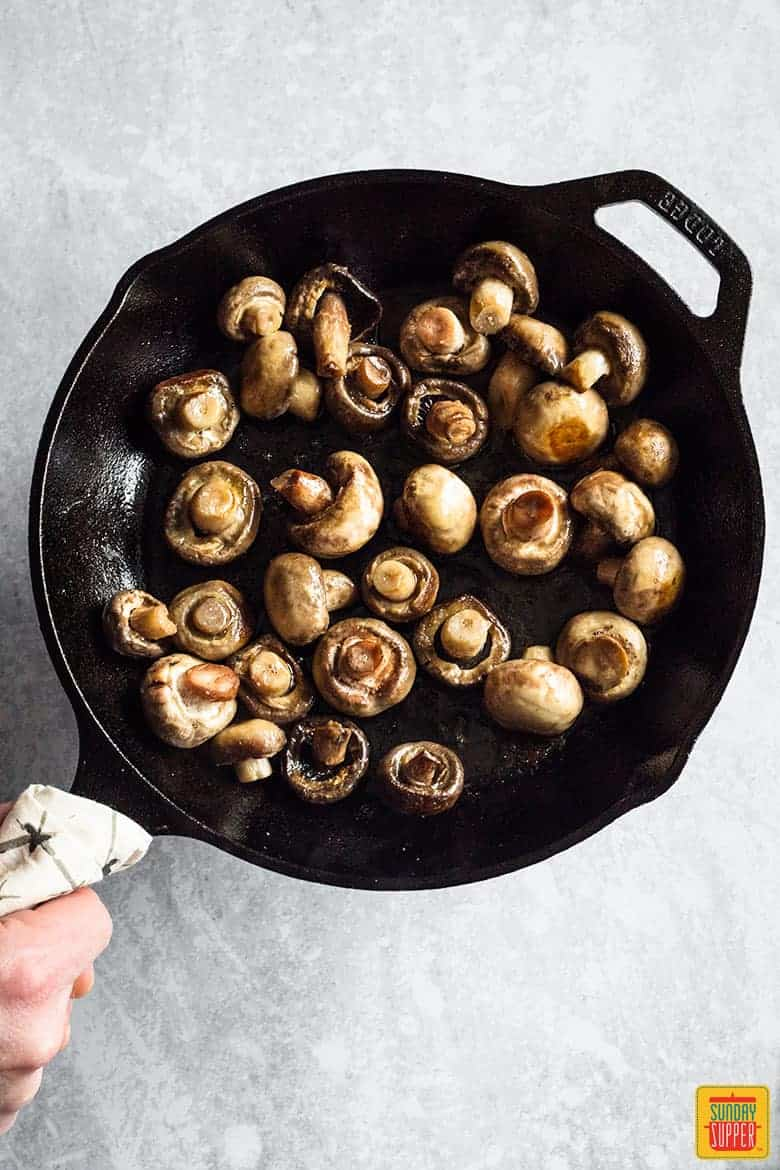 Button mushrooms in a cast iron skillet cooking