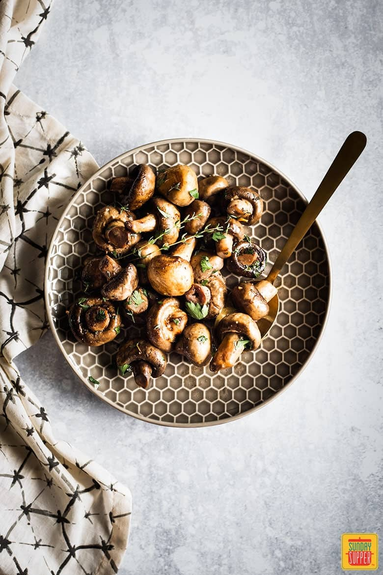 Cooked button mushrooms on a hexagonal pattern plate