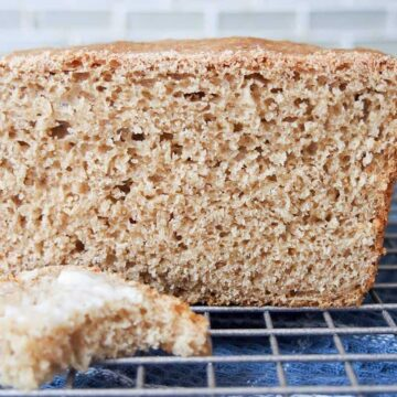 Loaf of sprouted bread with one slice cut and buttered