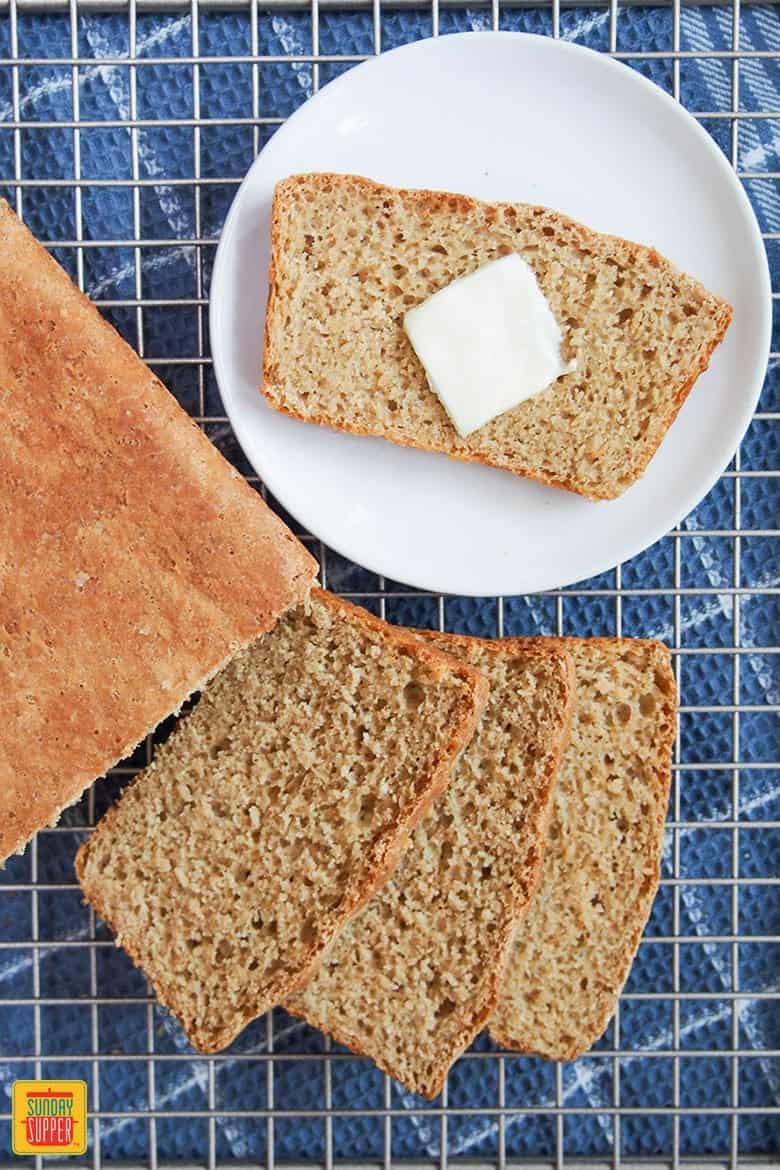 A slice of sprouted grain bread with a pad of butter on a white plate
