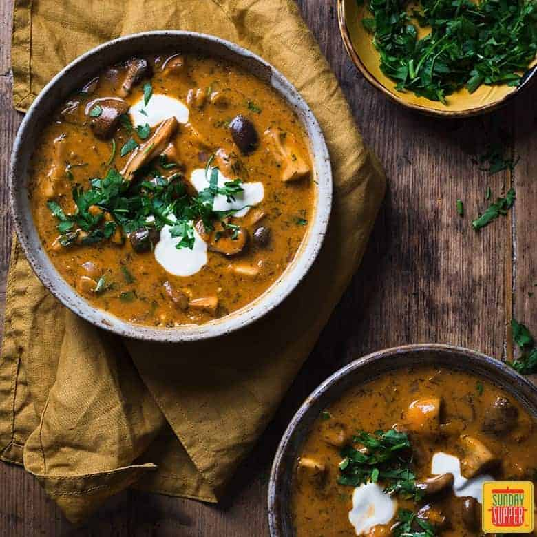 hungarian mushroom soup served with fresh chopped parsley and sour cream in bowls
