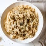 Mushroom risotto recipe served in a white bowl with a fork