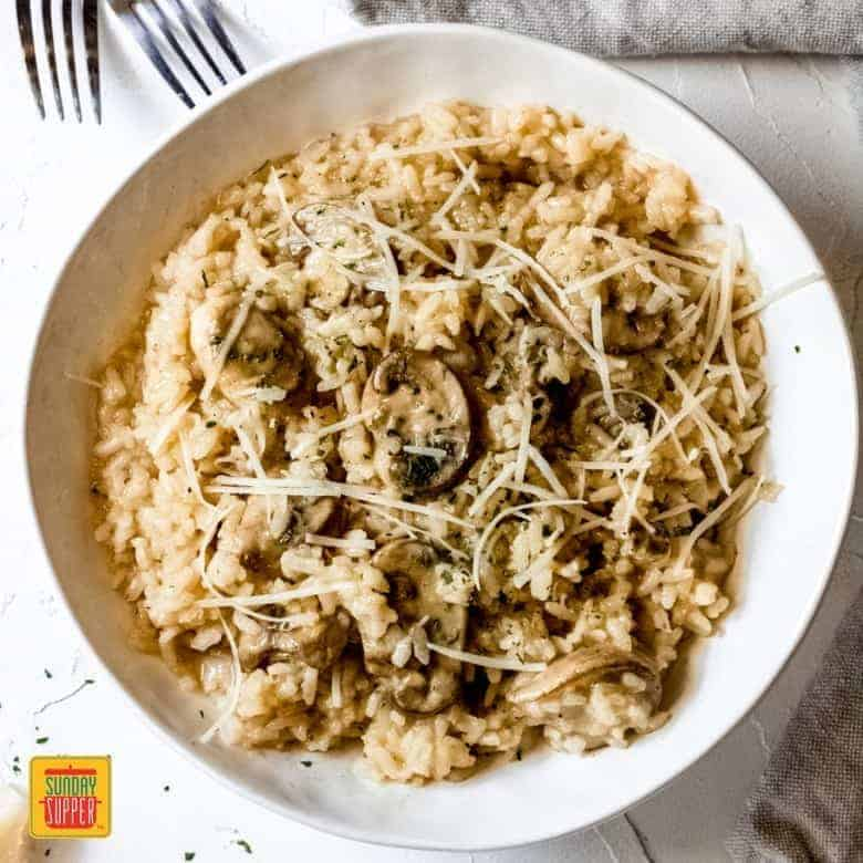 Mushroom risotto recipe served in a white bowl topped with Parmesan