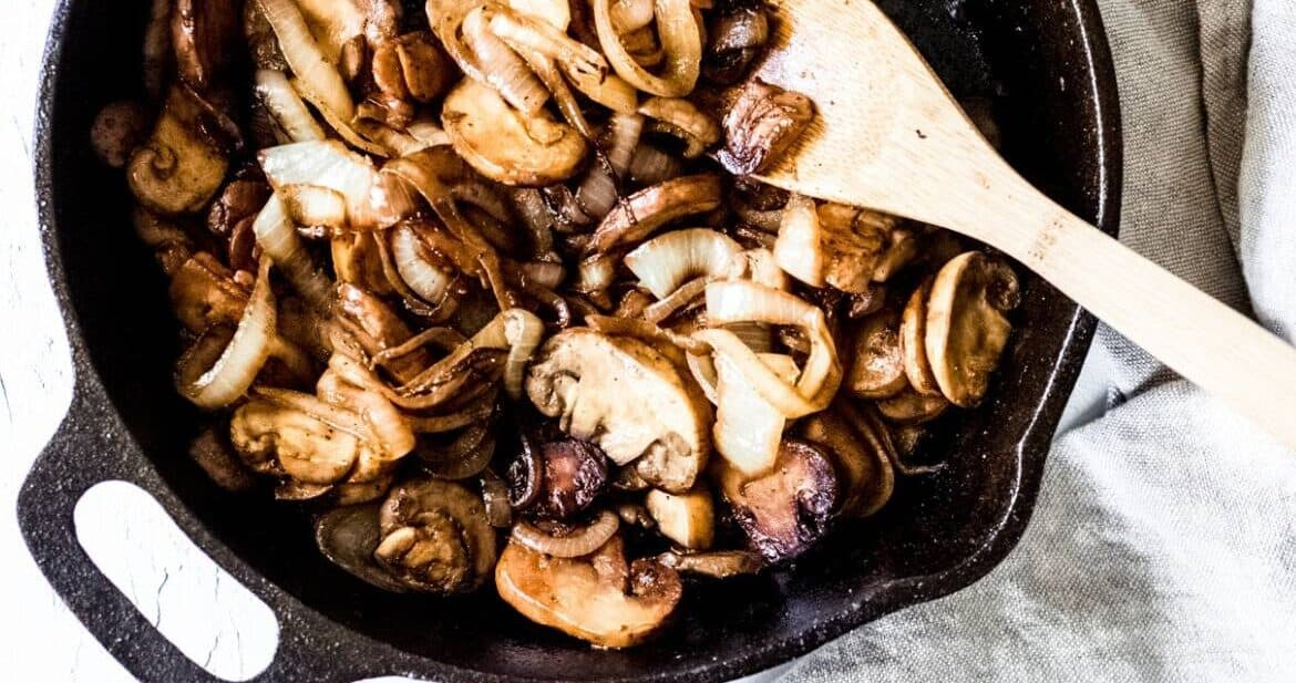 Sauteed mushrooms and onions cooking in a skillet with a wooden spoon