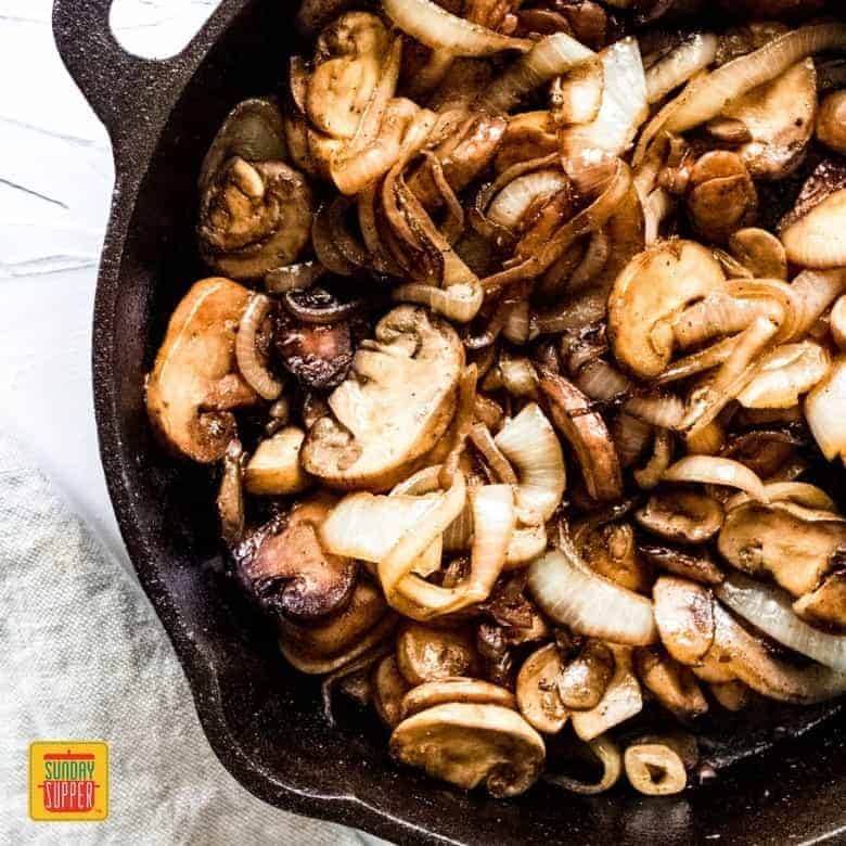 sauteed mushrooms and onions in a black cast iron skillet