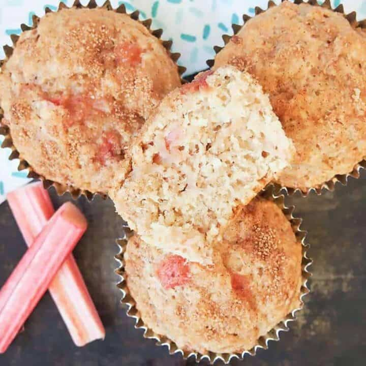 Four rhubarb muffins stacked next to two slices of fresh rhubarb