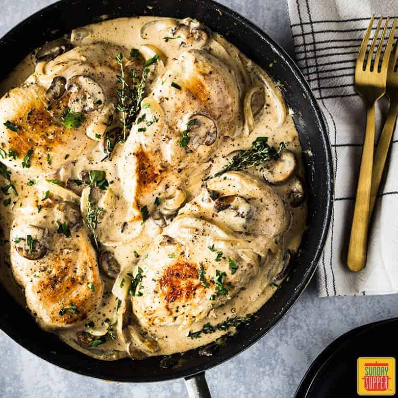 chicken breast and mushroom recipe in pan with fresh parsley and thyme for garnish