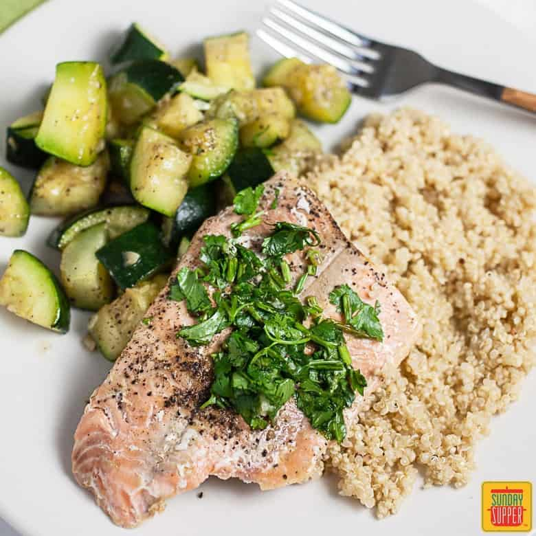 A cooked fillet of salmon with fresh gremolata served with roasted zucchini