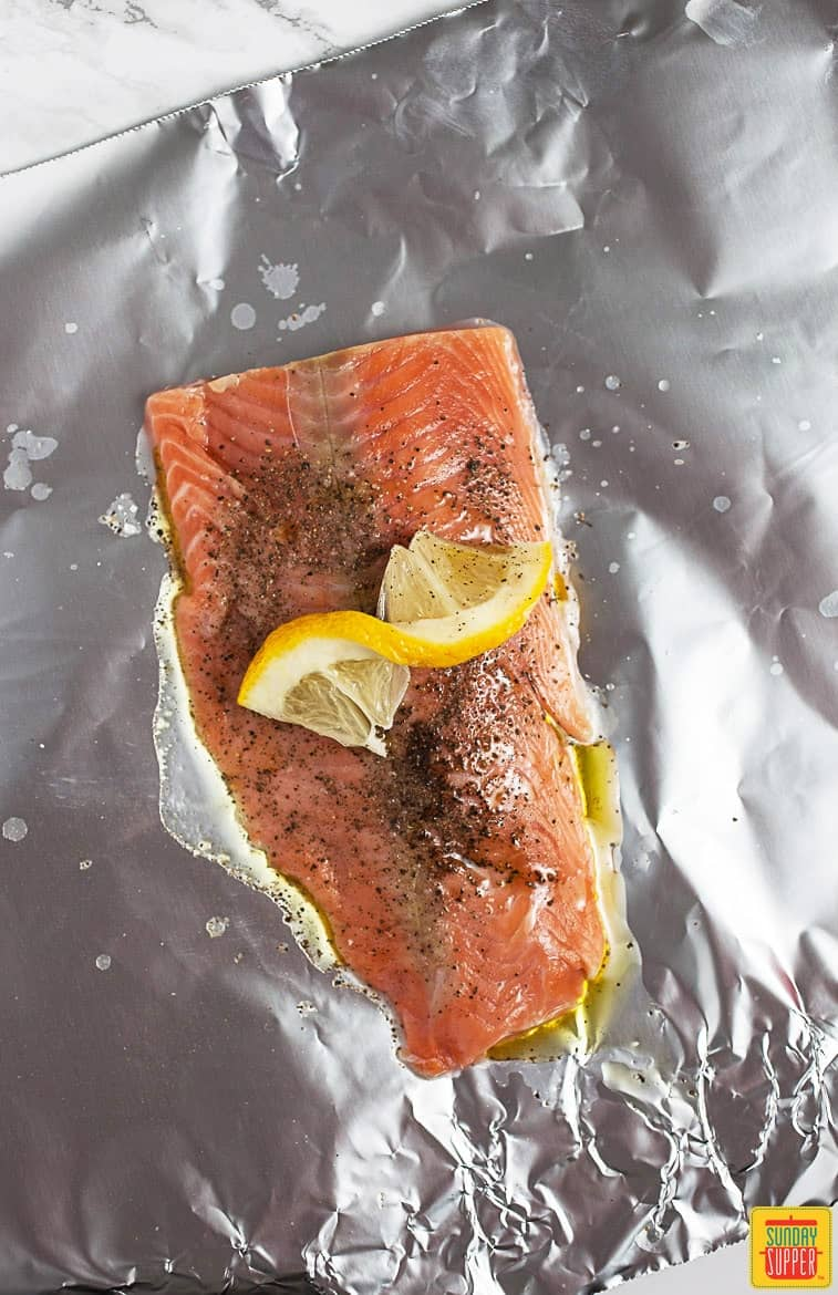 Uncooked Salmon topped with seasoning and a twist of lemon on a sheet of foil for foil pack salmon recipe