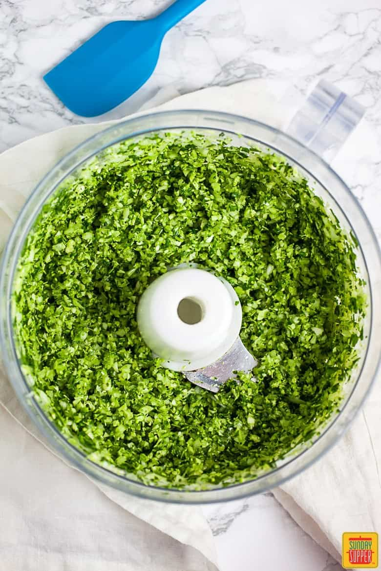 Pulsing broccoli florets, spinach, garlic, and onions in a food processor for veggie burger patties