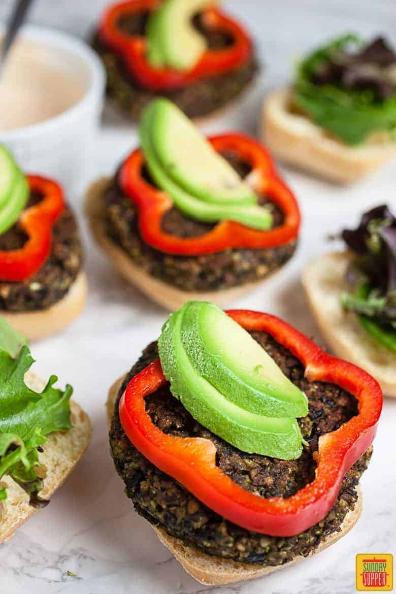 Black bean and mushroom burgers on buns with fresh avocado and sliced red bell pepper