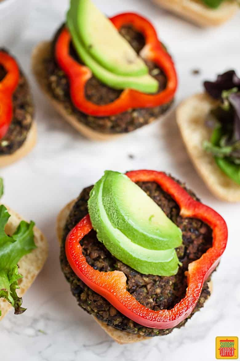 Black bean burgers served on a bun with fresh avocado slices and a sliced red bell pepper