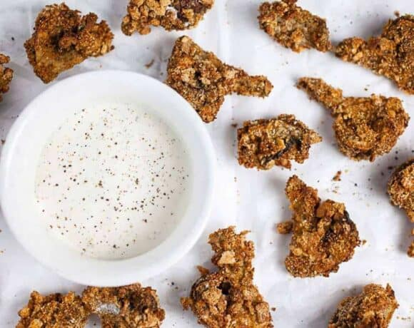 Air fryer mushrooms on white parchment paper next to ranch dipping sauce in a bowl