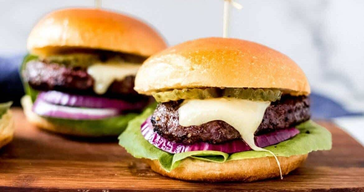 two bison burgers on a wooden cutting board