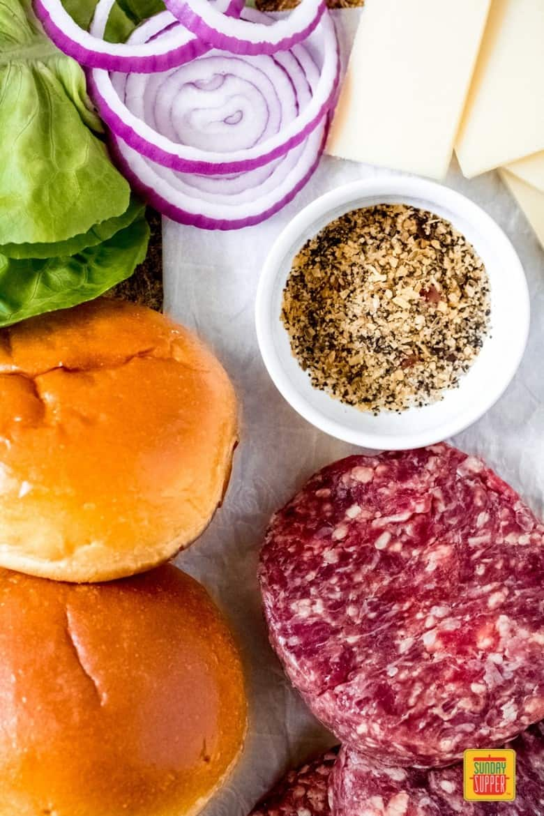 ingredients for bison burger recipe on parchment paper, including cheese slices, red onions, lettuce, buns, seasoning in a cup, and the bison meat