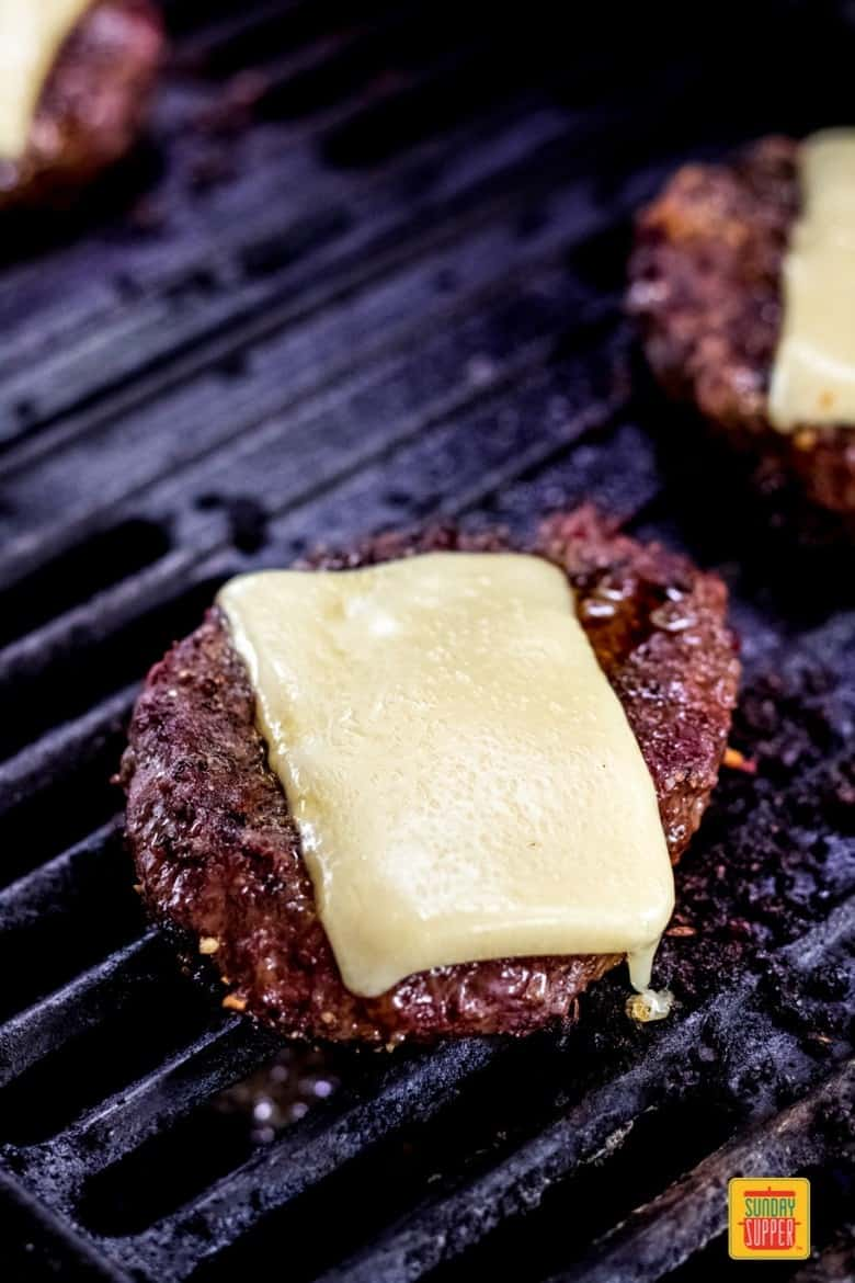 bison burgers on the grill topped with gruyere cheese