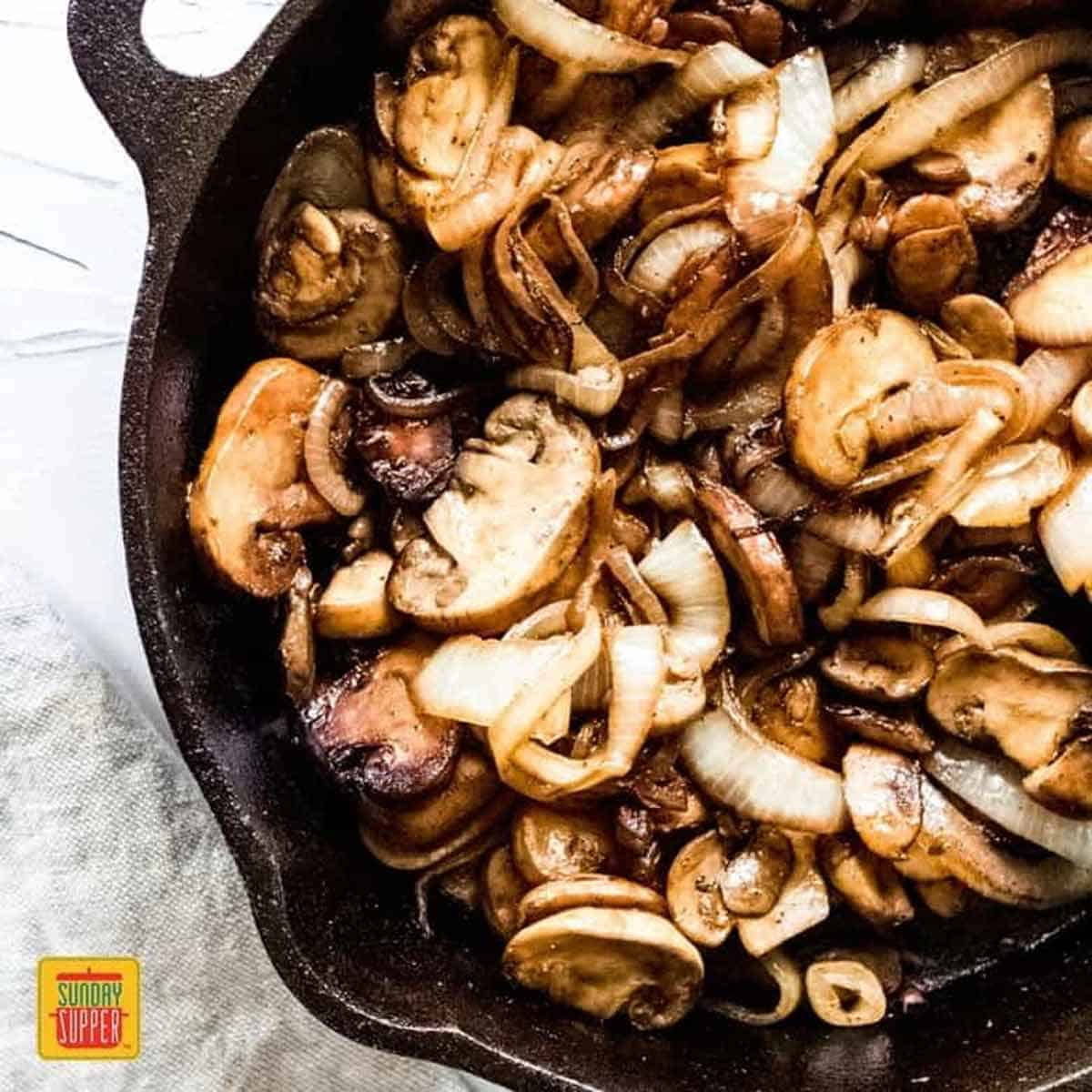 Sauteed Mushrooms and Onions in a black skillet, caramelized and ready to serve