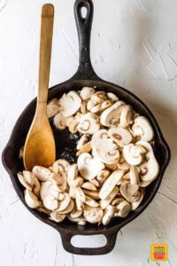 Sauteing mushrooms in a black skillet with a wooden spoon
