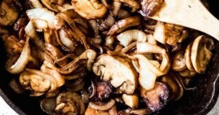 Sauteed onions and mushrooms in a cast iron skillet caramelized and ready to eat