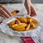 eating baked crispy potato wedges