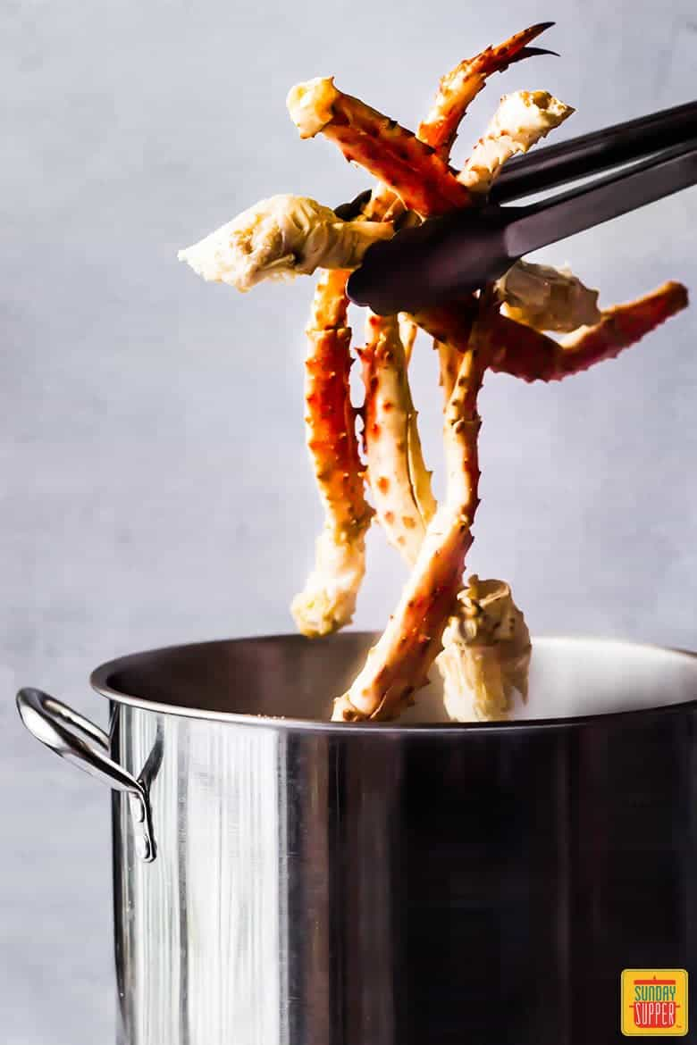 Steamed Crab Legs Recipe - lifting crab legs out of pot after cooking