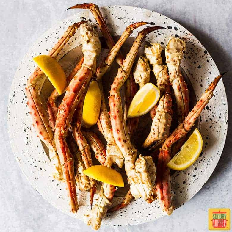 King crab legs on a speckled white plate with fresh lemon slices